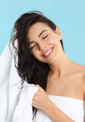 Young woman drying hair with towel on light blue background